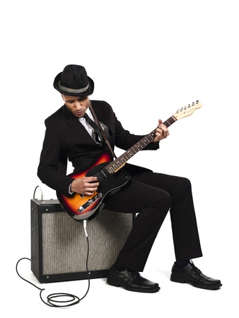 Young businessman sitting on the speaker and playing guitar against white background, Model: Kareem Duhaney photo