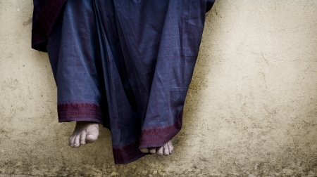 A woman sits on a wall and dangles her feet down