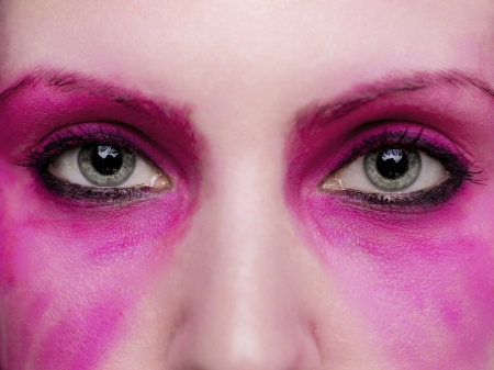 smeared: A close up on a pair of eyes surrounded by hot pink make up.