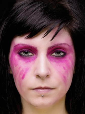 smeared: A goth woman with intense pink make up around her eyes,