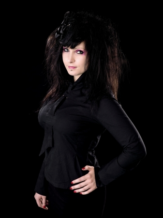 A gothic woman dressed in all black looks into the camera.