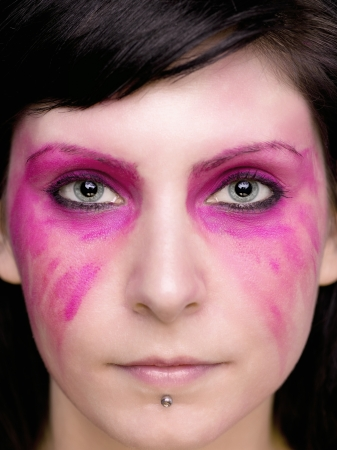 smeared: Make up is smeared from the eyes downwards.