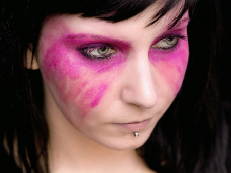 smeared: A woman with pink make up smeared on her face looks away from the camera.