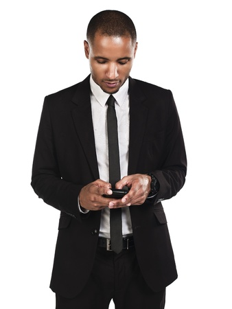 Young businessman texting on cellphone against white background photo