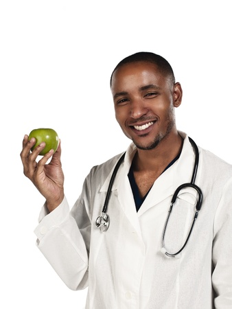 Young doctor holding green apple over white background photo