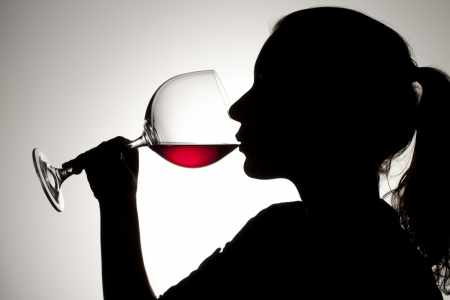 person appetizer: Silhouette shot of a female drinking red wine. Stock Photo