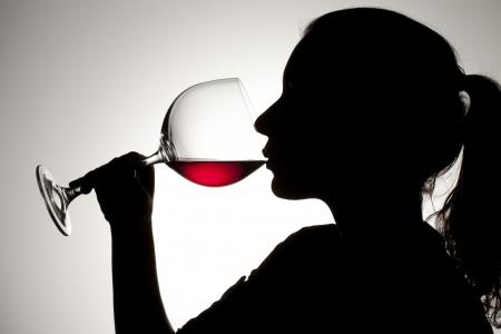 bebiendo vino: Silueta de tiro de una mujer beber vino tinto. Foto de archivo