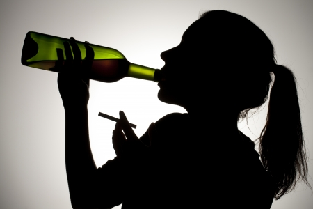 A close- up silhouette of a woman drinking wine and smoking a cigarette Stock Photo - 17134659