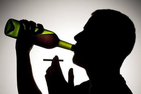 A silhouette of man drinking wine and holding a cigarette stick