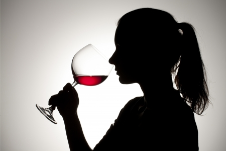 woman drinking wine: Silhouette shot of a female drinking red wine. Stock Photo
