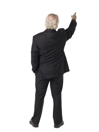 白い背景に対して何かを指す古いビジネスマンの背面図の完全な長さの肖像画