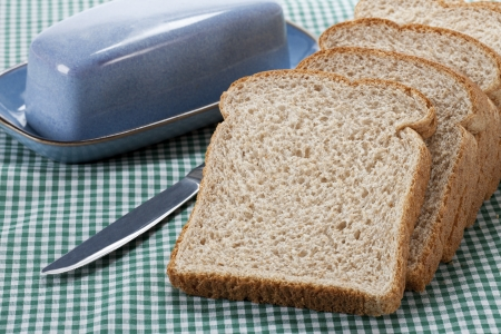 Close-up of brown bread with knife on table cloth. Stock Photo - 17134799