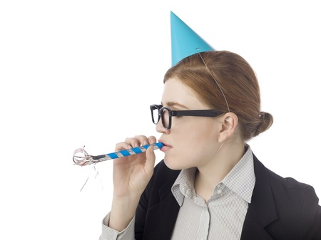 noisemaker: Close-up image of a young businesswoman with party hat and blower whistle celebrating on a white background Stock Photo