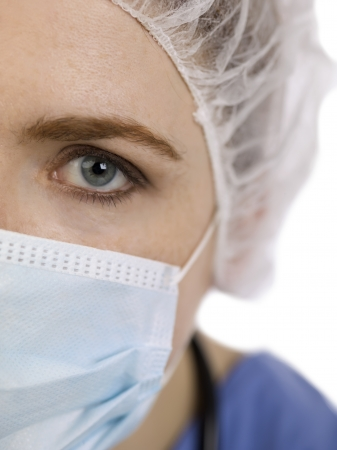 cropped image: Close-up cropped image of a face of a female surgeon looking at the camera on a white background