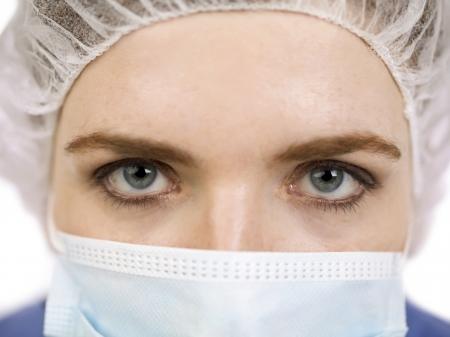 medical mask: Close-up cara de una mujer m�dico con mascarilla m�dica y redecilla aislado en un fondo blanco