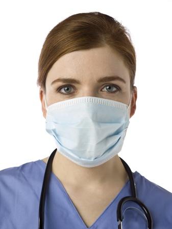 Close-up beeld van vrouwelijke verpleegkundige dragen van een gezichtsmasker tegen een witte achtergrond