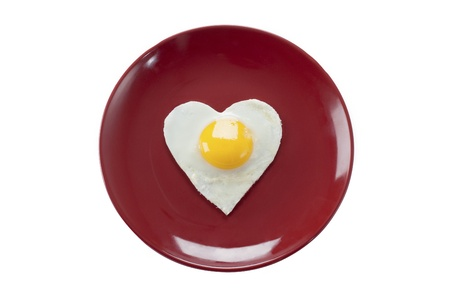 Fried egg in heart shape served in a plate over white background. photo