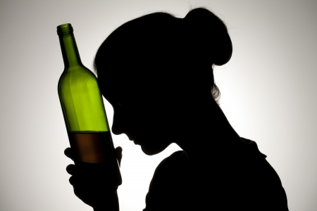 Silhouette shot of a woman holding a wine bottle close to her head.