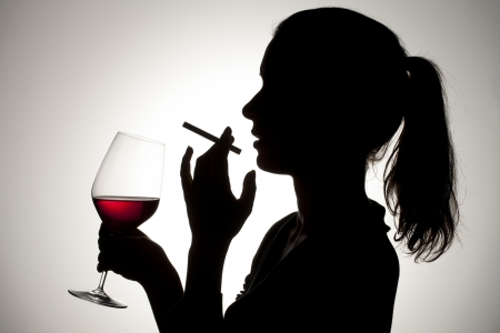 Silhouette shot of a female smoking a cigarette and holding a red wine glass. photo