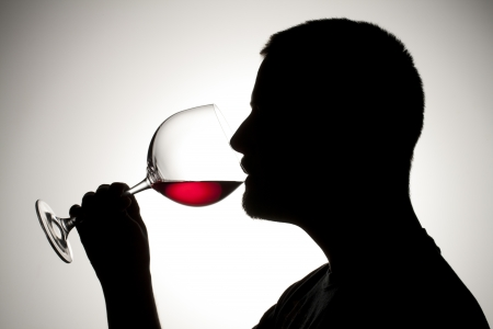 Silhouette shot of a man drinking red wine.