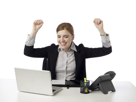 Portrait of a joyful businesswoman raising her fists in the air photo