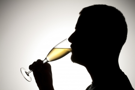Silhouette of a man drinking a wine photo