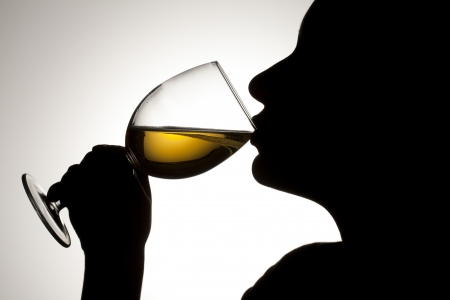 Silhouette shot of a person drinking white wine. Stock Photo - 17134551