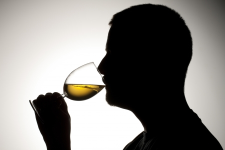 Side view silhouette of a man drinking white wine. photo