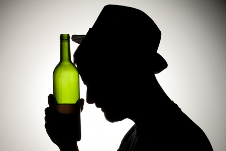 Silhouette of a man wearing hat holding wine bottle close to his head. Stock Photo - 17134650