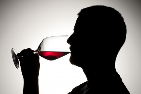 Image of a silhouette man while sipping wine isolated on a dark background Stock Photo