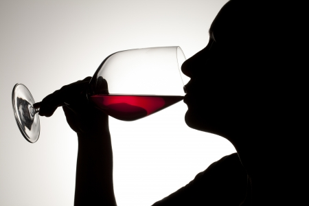 A close-up image of dark woman drinking red wine isolated