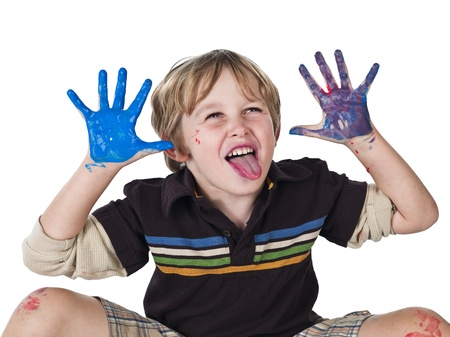 about age: Elementary boy with paint on his hands and sticking out tongue,
