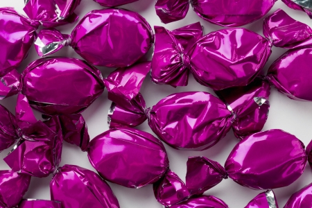 Extreme close-up view of shiny purple hard candies over white background. photo