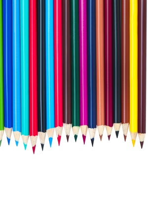 Various coloured pencils lay on a white background. photo