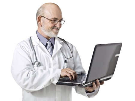 sagacious: Old doctor using a laptop isolated in a white background Stock Photo