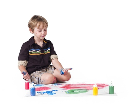 Elementary boy doing painting against white background. Stock Photo - 17133396