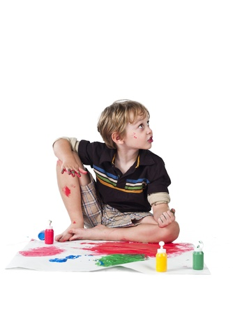 Elementary boy doing painting and looking away over plain background. Stock Photo - 17135062