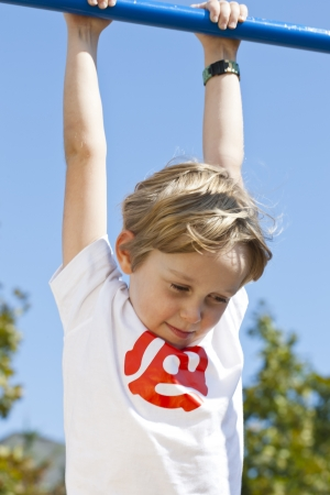 gripping bars: Elementary boy hanging on monkey bars and looking down with blue sky in the background,