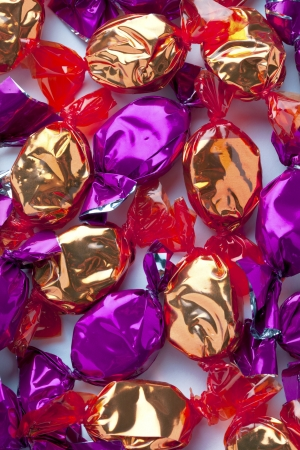 Golden and purple candies wrapped in shiny candy wrapper arranged randomly over white. photo
