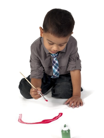 children painting: Image of a elementary boy busy painting over white background. Stock Photo