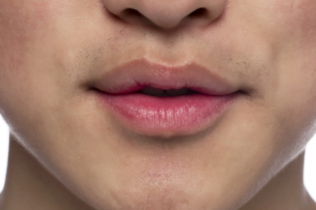 Close-up image of a mans lip over the white background