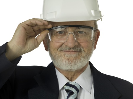 Closeup portrait of an old male architect wearing a helmet and safety glasses