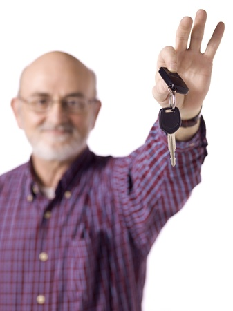Blurred image of an old man wearing long sleeve holding a car key isolated on a white background photo