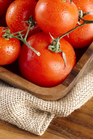 A pile of red ripe tomatoes on a wooden tray Stock Photo - 17135290