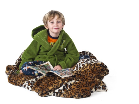 Portrait of a boy with blanket and comic book over white background, photo