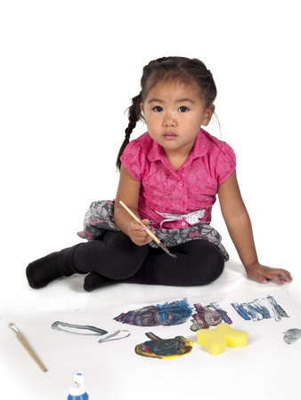 Portrait of cute girl with paint brush and paper against white background. photo