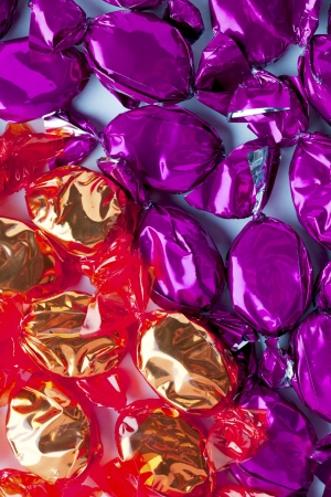 Close-up shot of hard candies wrapped in shiny golden and purple candy wrapper. photo