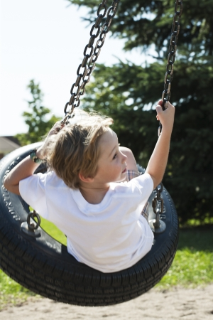 Rear view of a blonde boy swinging on tyre swing in a park, photo