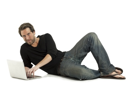 Close-up image of relaxed man lying on the floor using a laptop on the white surface Stock Photo - 17135105