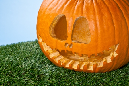 Pumpkin with a carved scary face sitting on a grass. photo